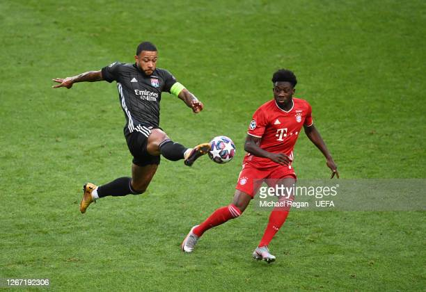 Memphis Depay of Olympique Lyonnais stretches for the ball as he battles with Alphonso Davies of Bayern Munich during the UEFA Champions League Semi...
