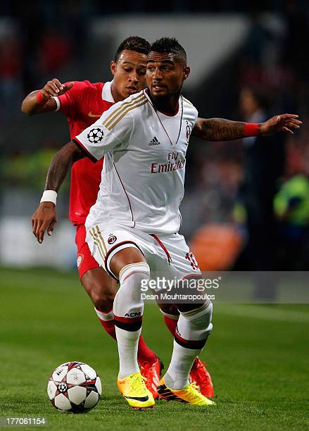 Memphis Depay of PSV and KevinPrince Boateng of AC Milan battle for the ball during the UEFA Champions League Playoff First Leg match between PSV...