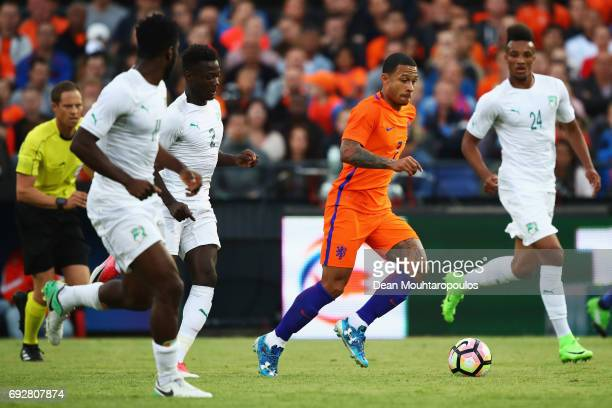 Memphis Depay of the Netherlands battles for the ball with Franck Kessie Nicolas Pepe and JeanPhilippe Gbamin of the Ivory Coast during the...