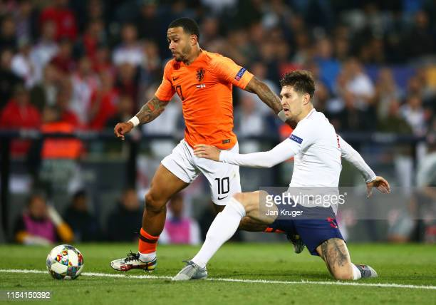 Memphis Depay of the Netherlands evades John Stones of England during the UEFA Nations League Semi-Final match between the Netherlands and England at...