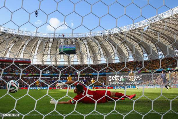 Memphis Depay of the Netherlands shoots and scores his team's third goal past Mathew Ryan of Australia during the 2014 FIFA World Cup Brazil Group B...
