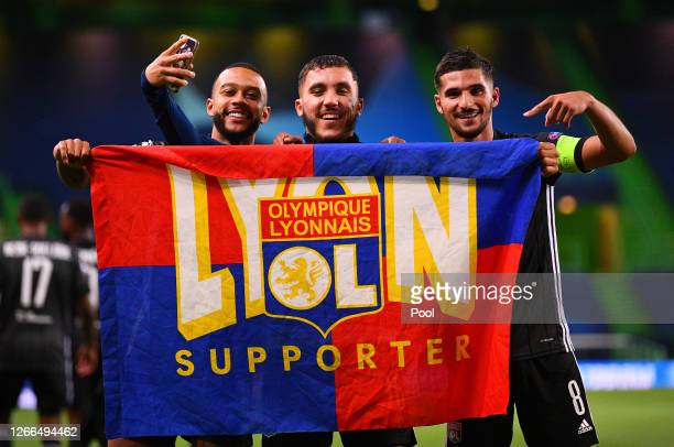 Memphis Depay, Rayan Cherki and Houssem Aouar of Olympique Lyon celebrate with a supporters flag following their team's victory in the UEFA Champions...