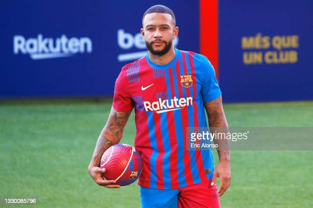 Memphis Depays of FC Barcelona reacts whilst posing for a photograph as he is presented as a FC Barcelona player at Camp Nou stadium on July 22, 2021...