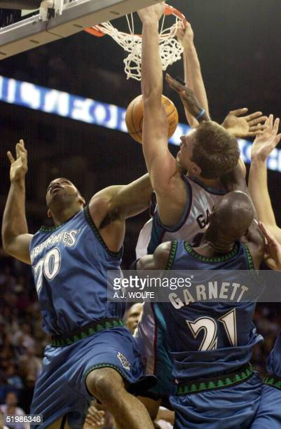 Memphis Grizzlies' Pau Gasol of Spain gets fouled by Minnesota Timberwolves' defenders Gary Trent and Kevin Garnett as he slams the ball in the third...
