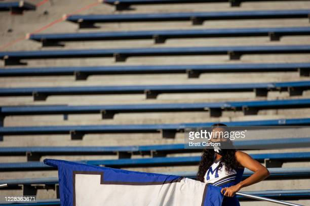 Memphis Tigers cheerleader looks on from the stands with a team flag while wearing a face covering before the game against the Arkansas State Red...