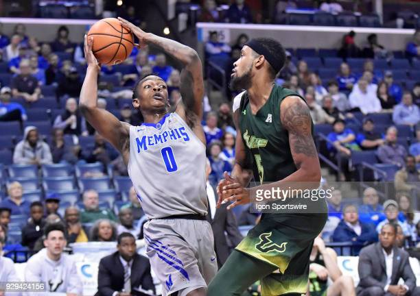 Memphis Tigers forward Kyvon Davenport tries to keep his balance amongst a South Florida Bulls defender during the first half of an NCAA college...