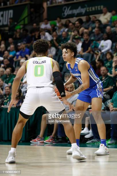Memphis Tigers guard Lester Quinones is defended by South Florida Bulls guard David Collins during the college basketball game between the Memphis...