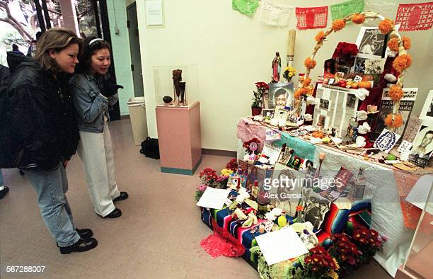 MEmuertosofrenda1030AAG––Rancho Santiago students Lizbeth Escutia and Lucy Dietrich 19 admire the ofrenda or altar in the school library The altar...