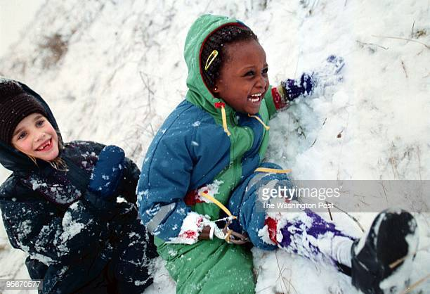 Memunatu Mansaray laughs Alicia Giauque, 7 as she tries to help her up the snow bank during the African children's first snowfall. Memumatu is being...