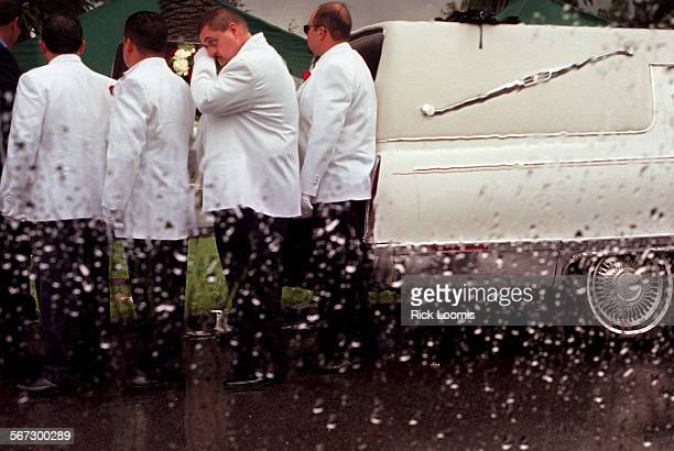 MEmurofuneralcasket0407RL––Santa Ana––A pallbearer wipes his eye as he helps move the casket of Jesse Muro through a gentle rain to his burial site...