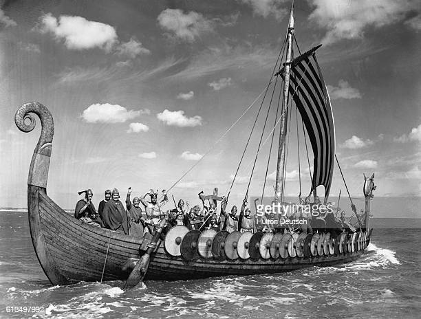Men aboard the Viking longship Hugin wave as they come to land at Broadstairs