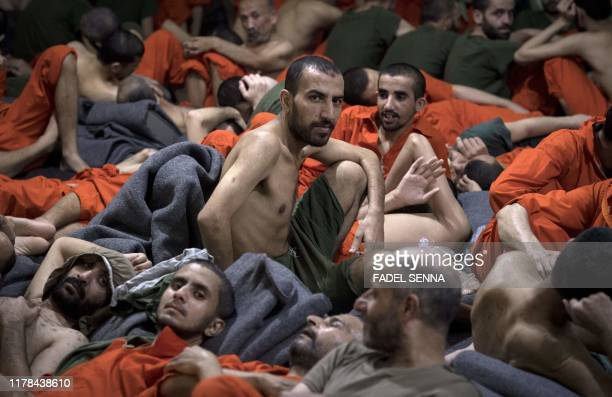 Men, accused of being affiliated with the Islamic State group, sit on the floor in a prison in the northeastern Syrian city of Hasakeh on October 26,...