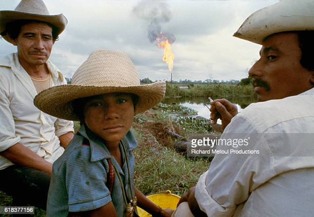 Men and a boy from a Mexican village sit as an oil well burns in the background Poverty coexists with oil wells in the village of Santa Maria in the...