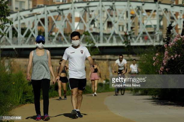 Men and a woman are seen walking next to Segura river on the first day of reducing the Coronavirus, COVID-19 lockdown measures that allows adults to...