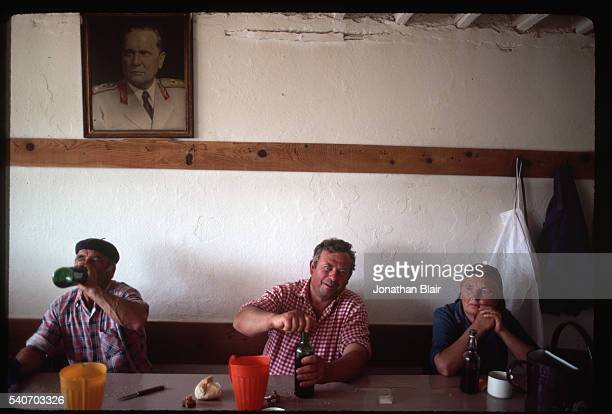 Men and a woman sit eating and drinking wine on their morning break known as a miranda at the Brac Stone Quarry in Pucisca Croatia Socialist Federal...
