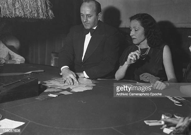 A men and a woman smoking playing poker at the San Remo Casino 1950
