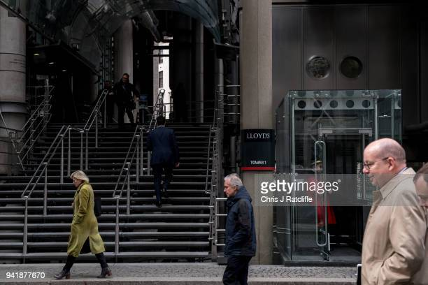 Men and a woman walk past and into the Lloyds building as the deadline nears for companies to report their gender pay gap on April 4 2018 in London...