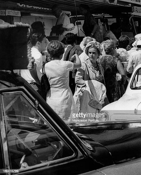 Men and along the street waiting in front of a restaurante among cars and buses a lady making a confused face turns her head around Capri Italy 1962