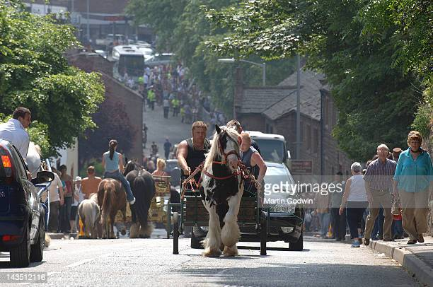 Men and boy riding on a cart drawn by a cart horse up the street in Appleby whilst a woman rides bareback at the Appleby Horse Fair Appleby Cumbria...