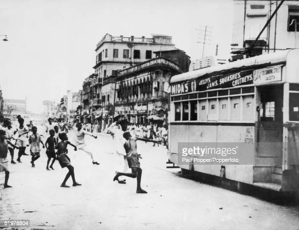 Men and boys join together to throw stones at a tram in Calcutta 1st April 1947