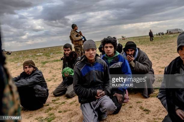 TOPSHOT Men and boys suspected of being Islamic State fighters wait to be searched by members of the Kurdishled Syrian Democratic Forces after...