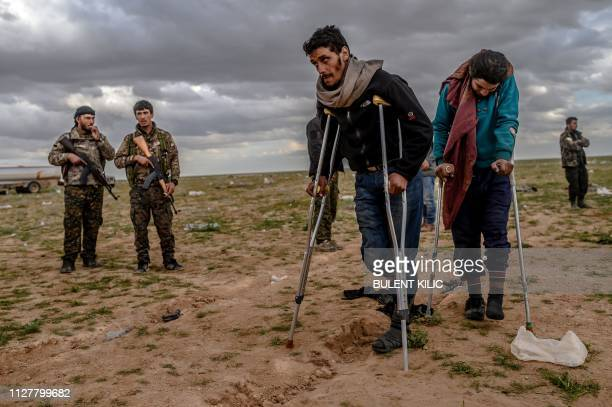 Men and boys suspected of being Islamic State fighters wait to be searched by members of the Kurdishled Syrian Democratic Forces after leaving the IS...