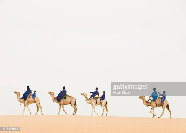men and boys traveling by camel - hugh sitton stock pictures, royalty-free photos & images