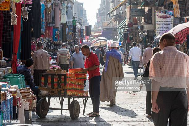 Men and covered women shopping in alleyway market