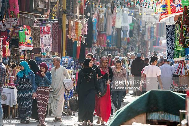 Men and covered women walking through market