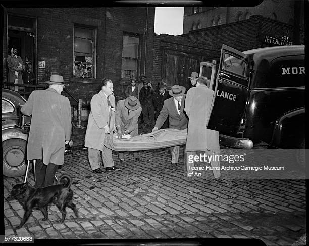 Men and deputy coroner Charles D Murphy with cigarette on left loading body into morgue ambulance with onlookers and dog on street in front of house...