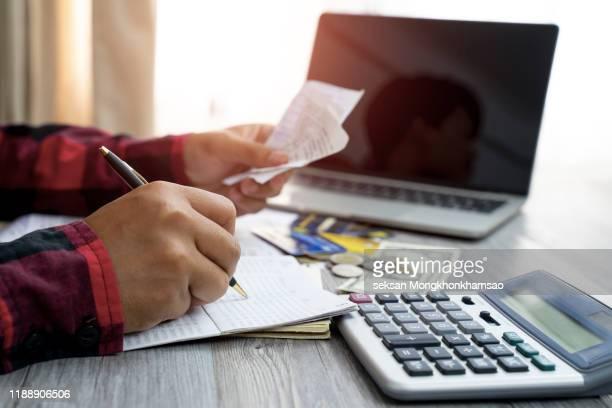 men and documents that calculate home office expenses - dívida imagens e fotografias de stock