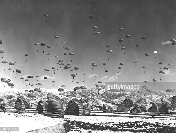 Men and equipment being parachuted to earth in an operation conducted by United Nations airborne units. Ca. 1951.