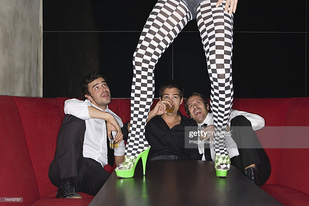 Men and legs of table dancer : Stock Photo