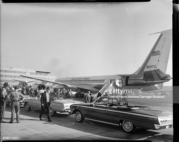 Men and police gathered around parked cars and Air Force One airplane during President Kennedy campaign stop Allegheny County Airport October 1962