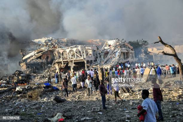 TOPSHOT Men and Somalian soldiers arrive on the site to rescue victims of the explosion of a truck bomb in the centre of Mogadishu on October 14 2017...