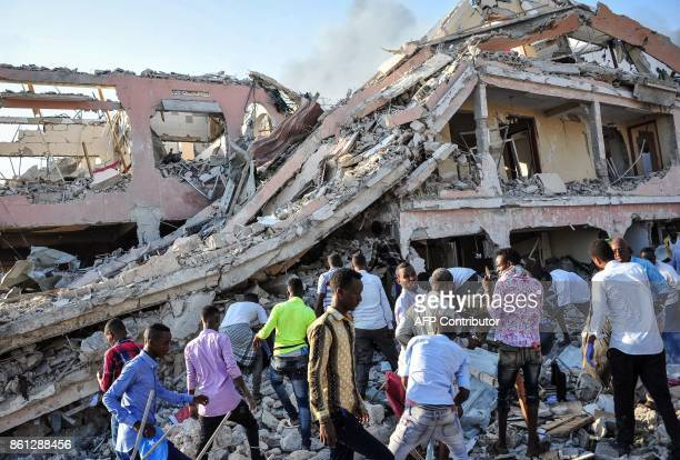 Men and Somalian soldiers arrive on the site to rescue victims of the explosion of a truck bomb in the centre of Mogadishu on October 14 2017 A truck...