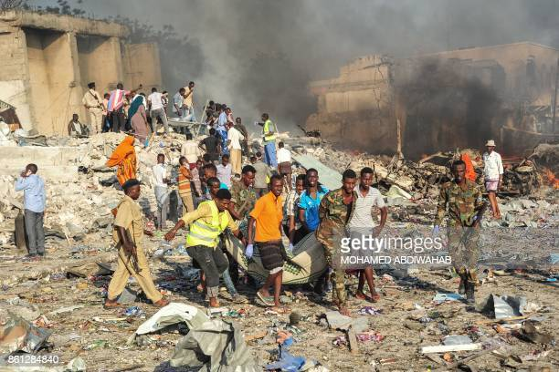 TOPSHOT Men and Somalian soldiers rescue victims on the site of the explosion of a truck bomb in the centre of Mogadishu on October 14 2017 A truck...