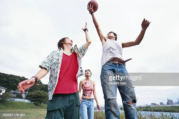 Men and woman playing football, outdoors, low angle view