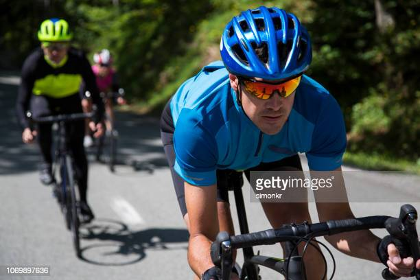 men and woman riding road bikes on mountain road - road cycling stock pictures, royalty-free photos & images
