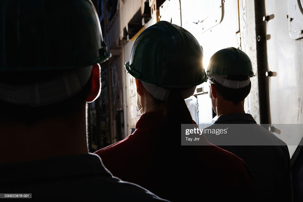 Men and woman standing between cargo containers, wearing hard hats : Stock Photo