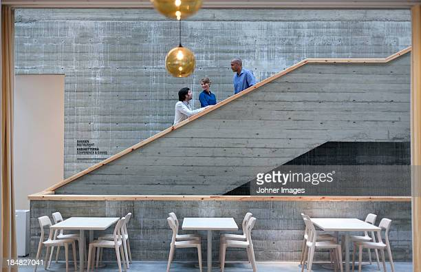 Men and woman talking on stairs