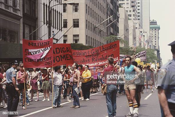 Men and women carry banners during the Gay Pride parade in New York City USA June 1983