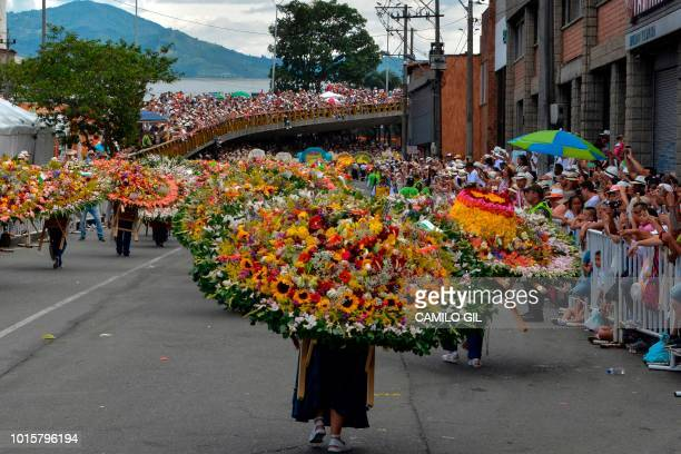 Men and women carry flower arrangements during the traditional Silleteros parade as people watch held as part of the Flower Festival in Medellin...