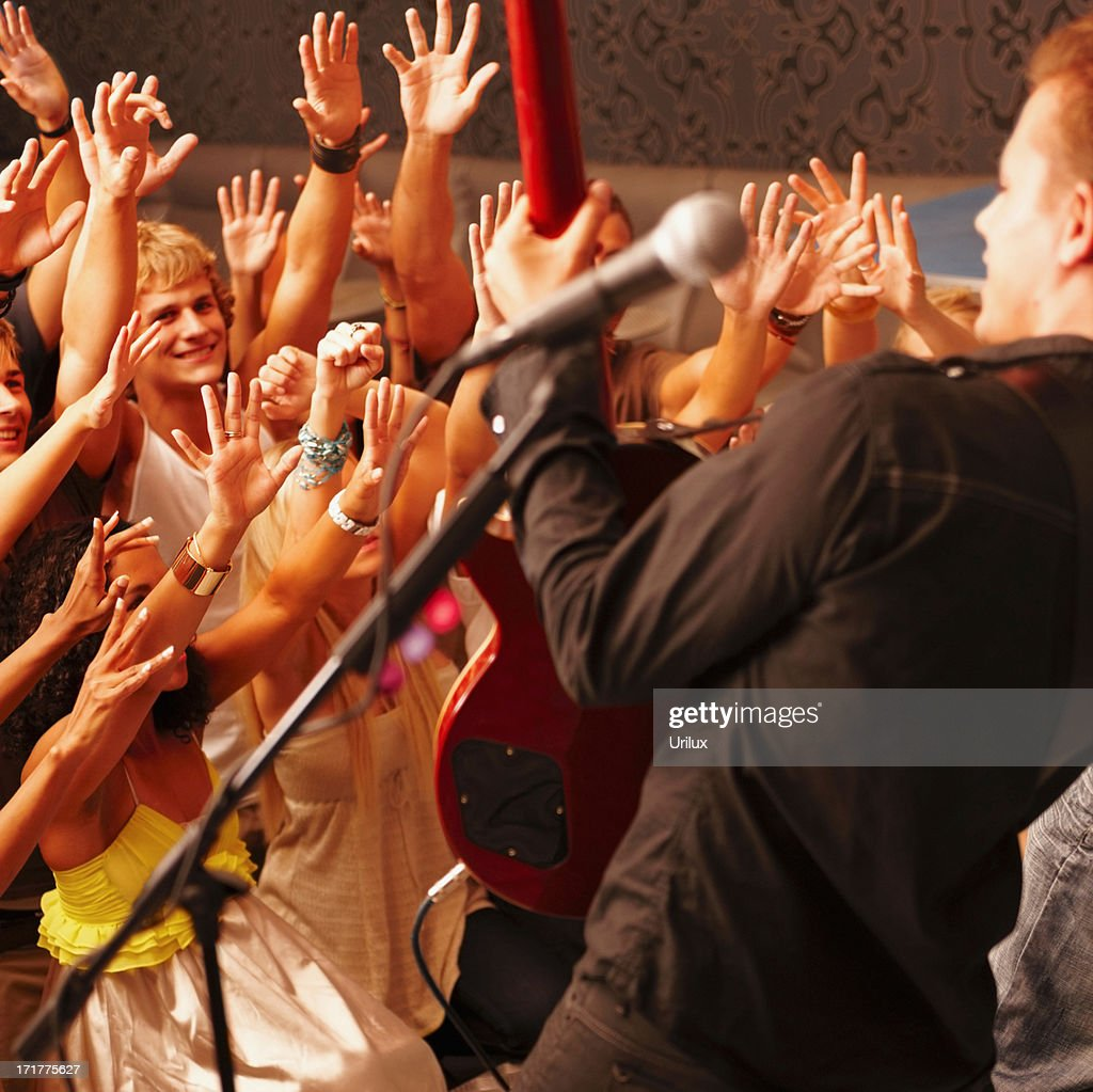 Men and women cheering a young guitarist : Stock Photo