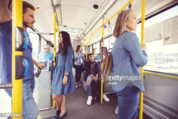 hombres y mujeres que viajan diariamente en transporte público - izusek fotografías e imágenes de stock