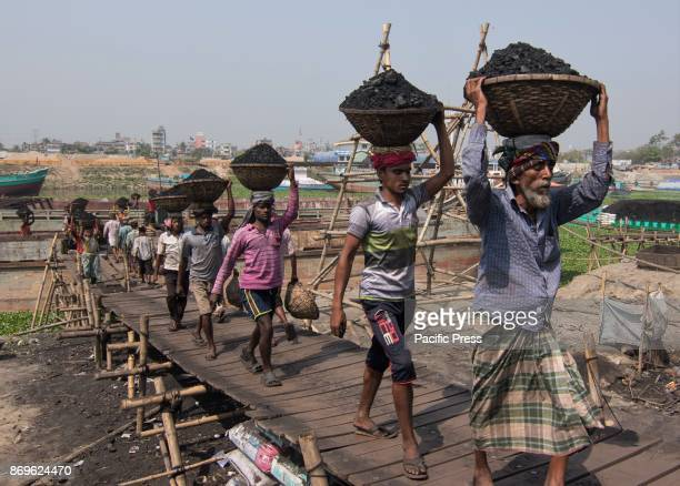 Men and women daily workers unloading coals from small ships in Turag river capital city Dhaka Bangladesh In the early morning workers starts...