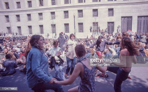 Men and women dance in a circle holding hands during demonstrations related to the Vietnam War May Day Protests Washington DC May 1971