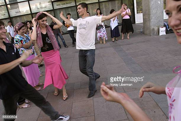 Men and women dance on the street performing traditional dances July 8 2005 in Bishkek Kyrgyzstan Standing in a circle the men sing and clap and...