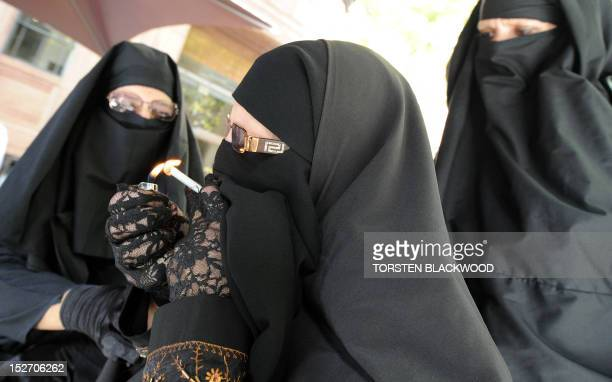 Men and women dressed in burqas from the group 'Faceless' try to smoke while calling for the banning of the conservative Muslim apparel throughout...