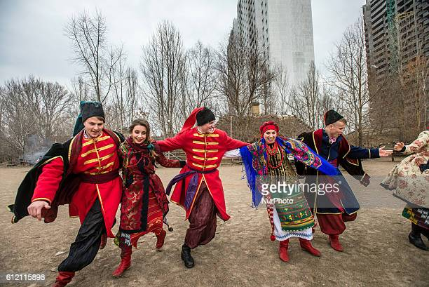 Men and women dressed in Ukrainian costumes perform traditional dances during Maslenitsa celebration in Mamayeva Sloboda Kyiv Ukraine on March 13 2016